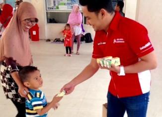 Sauqi Maulana, Corporate Communication PT Trio Motor membagikan susu gratis kepada anak-anak di Menara Pandang Siring Tendean Banjarmasin